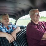 senior couple driving in big car