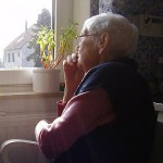 senior woman stares out window