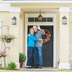 A happy senior couple standing together outside their home, at the front door, smiling and waving.