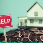 large pile of pennies in formt of a house with HELP sign