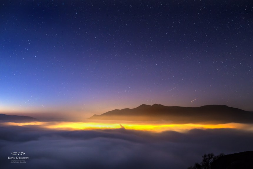 The lights of Keswick illuminate, from beneath, a rare evening cloud inversion – whilst above, a crystal clear sky hosts a galaxy of twinkling stars. View taken by David Jackson from Walla Crag
