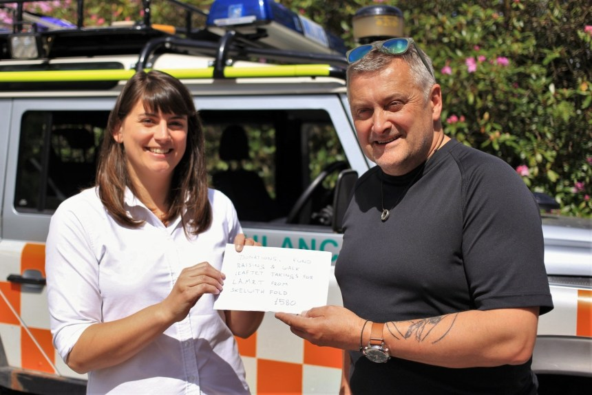 Skelwith Fold receptionist Kath Mort presents the park's donation to mountain rescue team leader Nick Owen