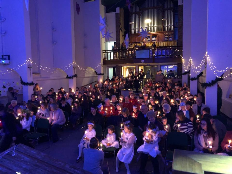 image of a congregation at St Barnabas celebrating a christmas service with candles