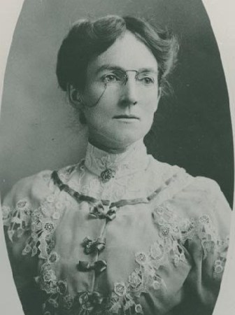 Black and white photographic portrait of Mary Malcolmson. She has her hair up and is wearing glasses and a blouse with a lace high-neck collar