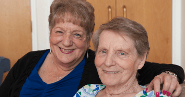 Two older women smiling at the camera