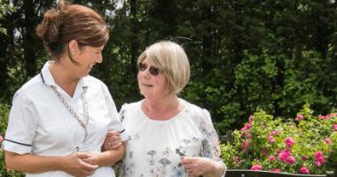 A woman and a nurse walk arm in arm through gardens