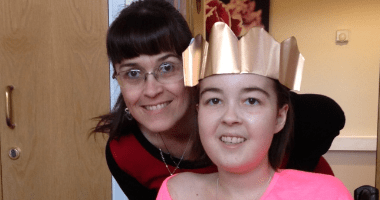 A young woman in a christmas hat next to her mother