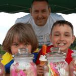 Kids standing behind jars full of sweets