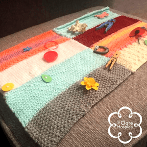 A Twiddleblanket - a blanket with novelty items attached onto it, such as pegs, buttons, flowers