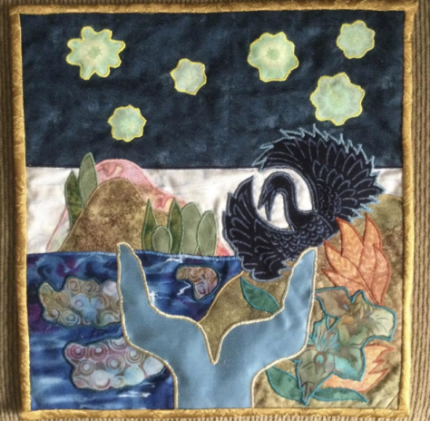 Scene in fabric collage of ocean with whale tale, swan, land, plants, glacier in distance