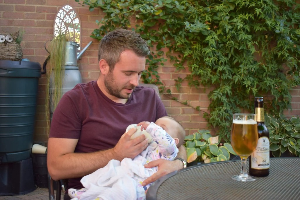 Tom Hallett founder of Steady Drinker feeding his baby daughter and drinking an alcohol-free beer