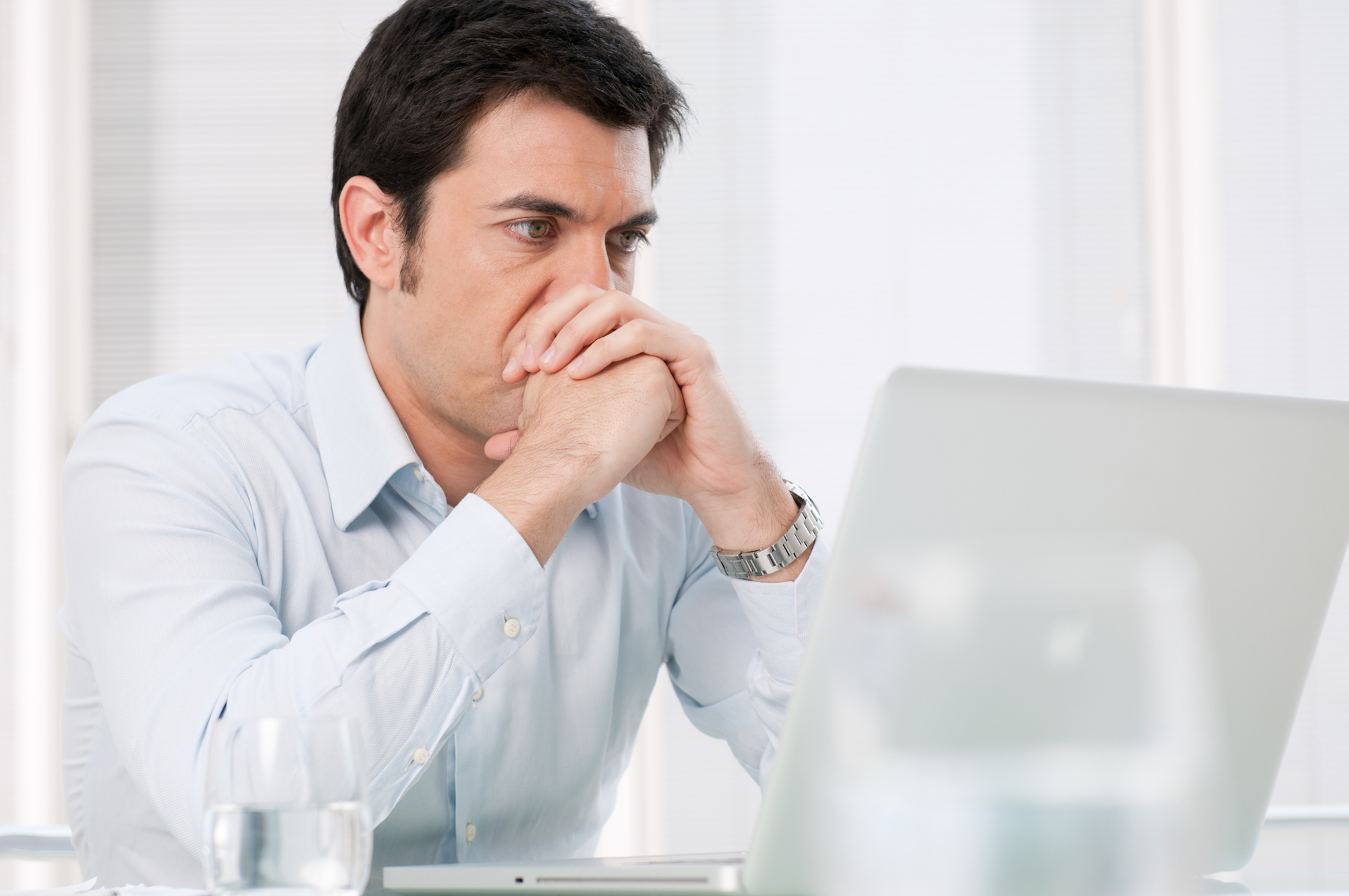 a man holding his two hands on a fist to his chin, looking at his laptop
