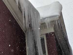 Ice dam hanging from roof erie