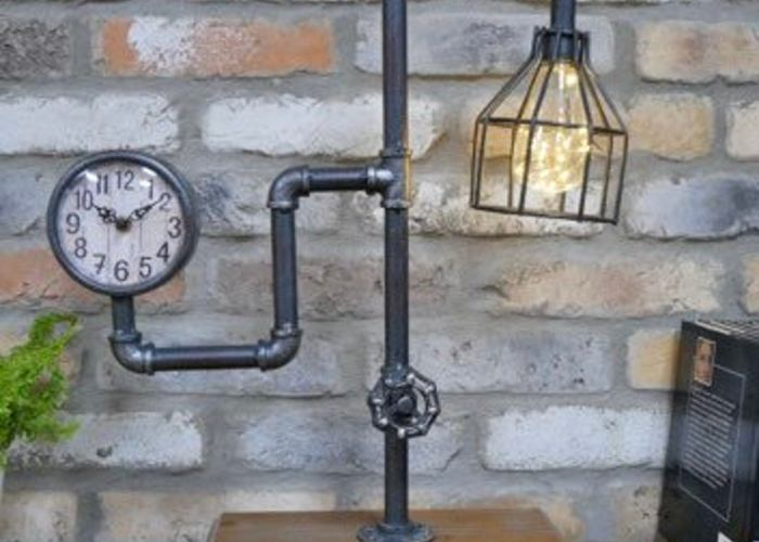 This stunning lamp made from metal pipes includes a working clock and sits on a wooden stand.