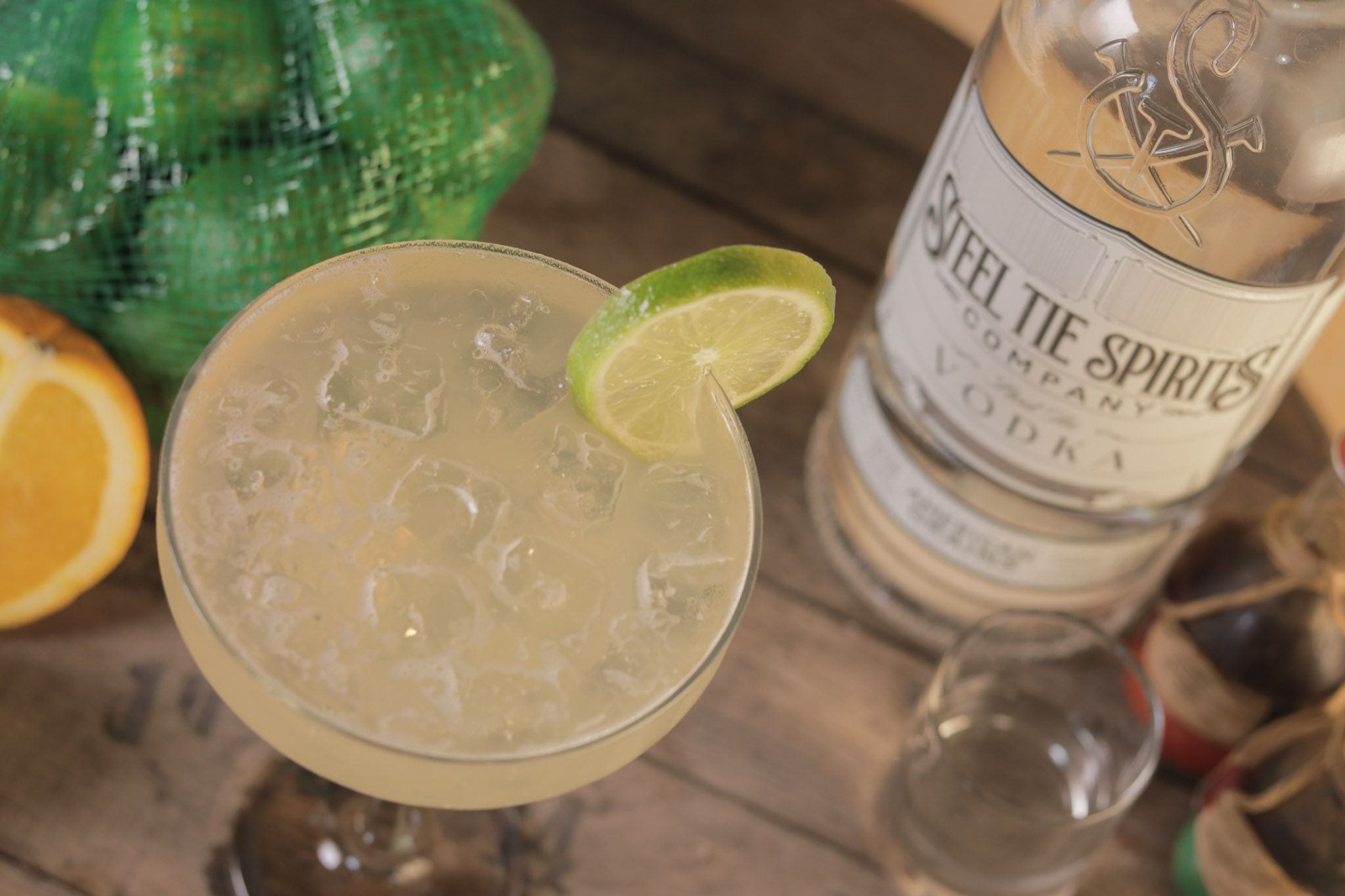 A margarita glass filled with vodka, lime and lemon juices sitting on a wooden surface