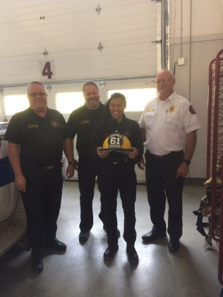 Firefighter Johnson receives her shield for completing her Jump Seat Qualifications.