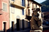 Fountain statuette and row of rustic houses