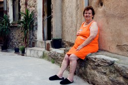 Old woman in orange relaxing outside her house