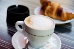 Cappuccino, croissant and ashtray