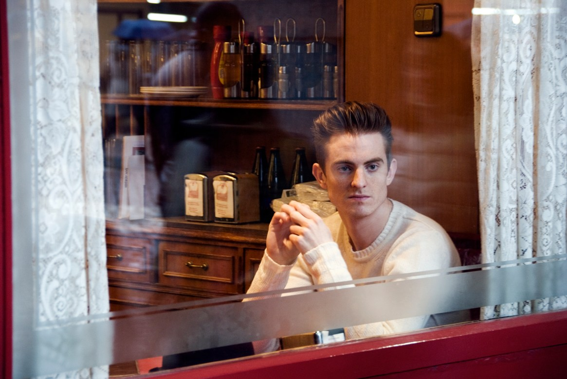 Man peering through a coffee shop window