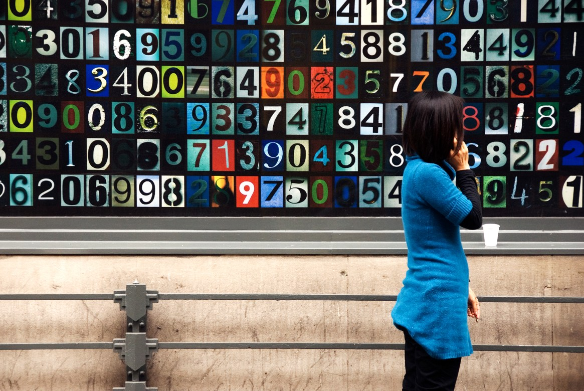 A woman in a blue dress talks on her phone, standing in front of a giant colourful numbers poster