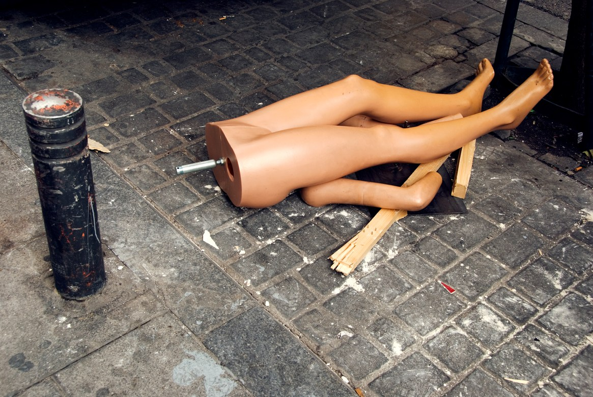 A headless, broken mannequin lies in the street
