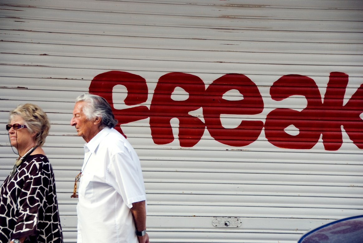 "A man and woman walk past read graffiti that reads ""freak"""