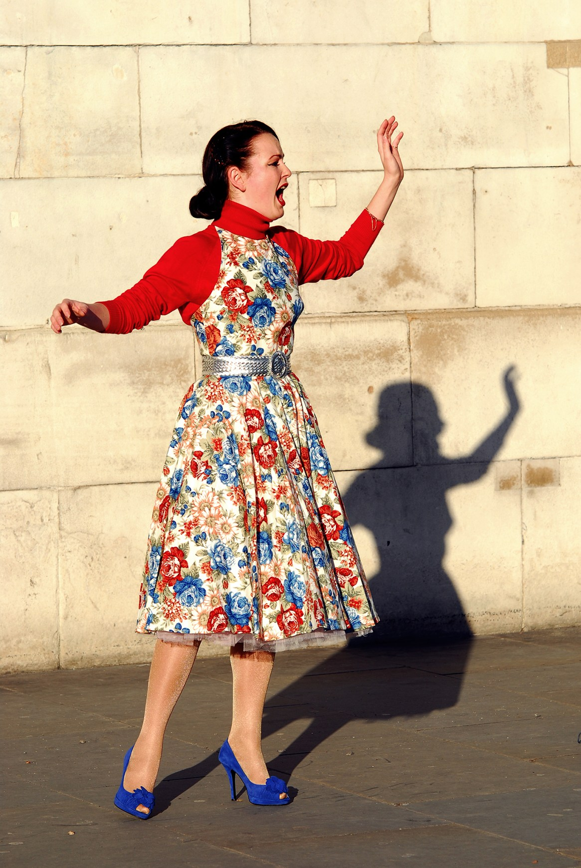 Street performer in red top and flowery dress singing opera on Trafalgar Square, London