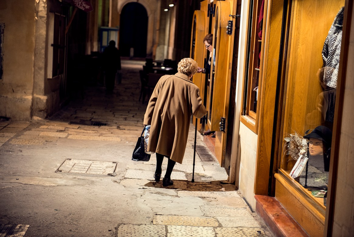 Woman in brown coat walks down a dimly lit alleyway in Valletta, Malta