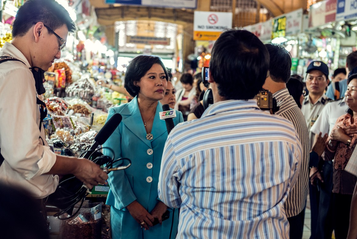 A local politician is interviewed in the middle of a bust market in Ho Chi Minh City