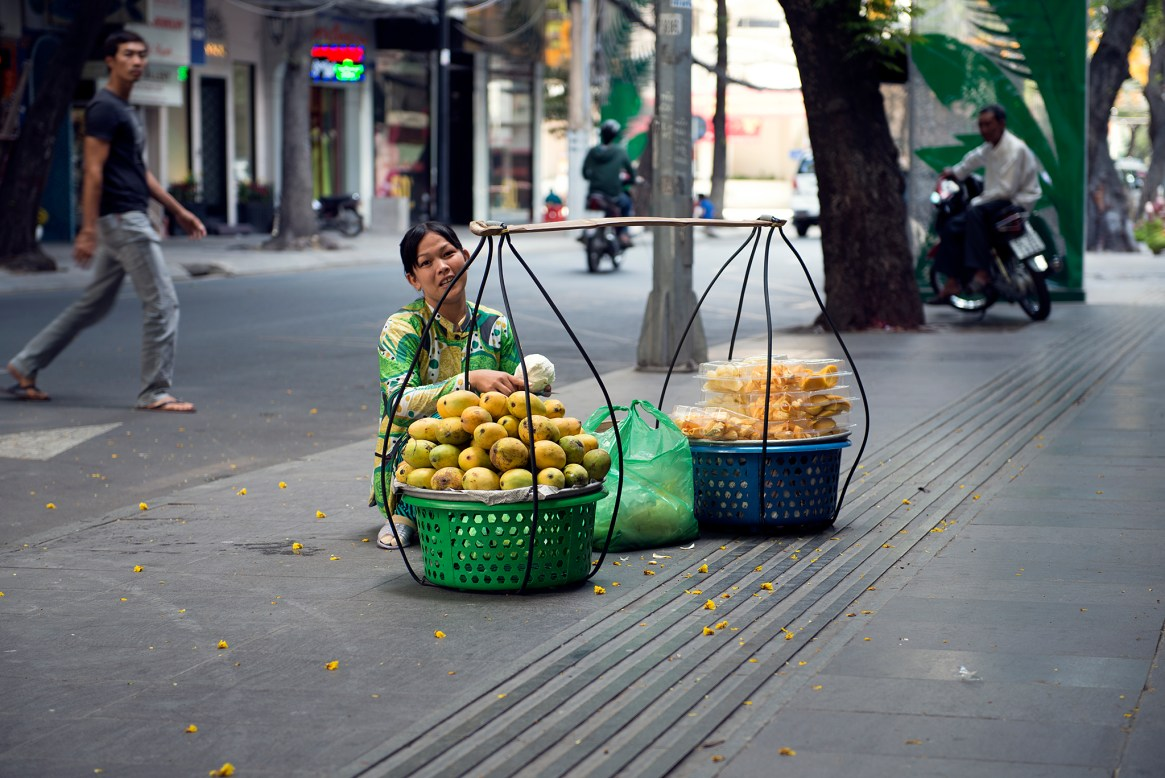 Vietnamese street vendor selling mangos and other fruit in Ho Chi Minh city
