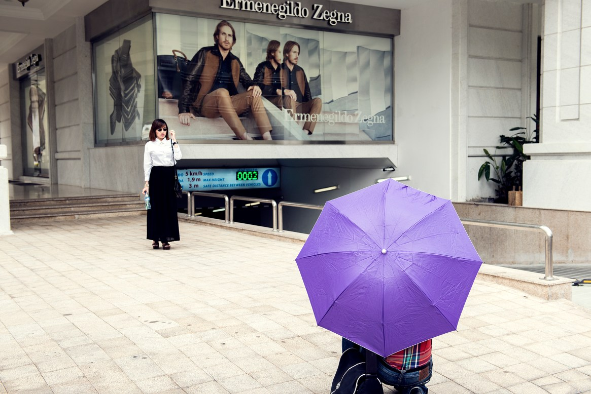 A person hiding behind a purple umbrella takes a picture of a woman in black and white posing in front of a fashion ad