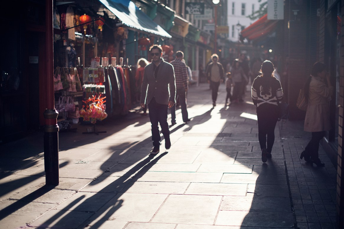 Landscape backlit shot of people walking down a side street with colourful shop fronts in Chinatown near Soho, London
