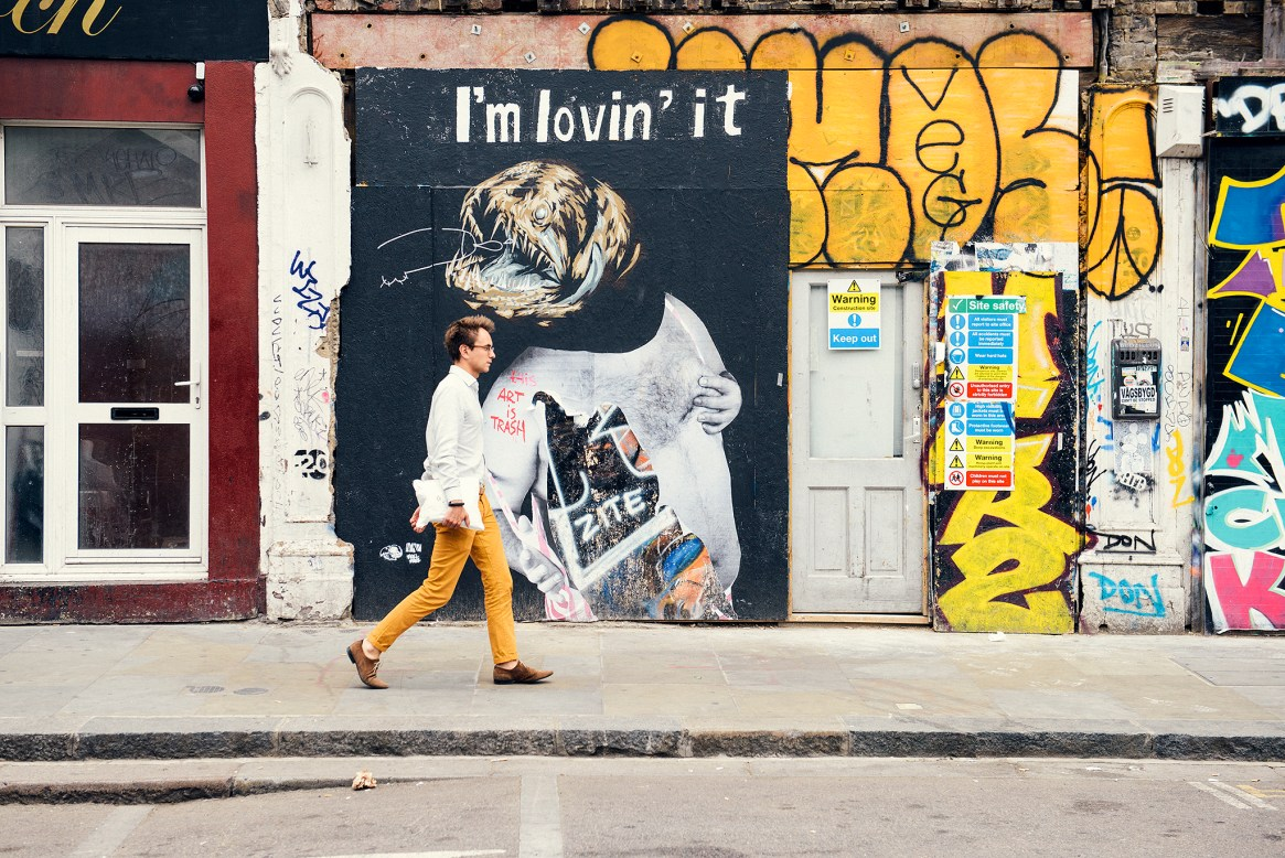 A man in yellow trousers walks past a wall with yellow graffiti and a piece of street art titled 'I'm lovin' it' in Shoreditch, London
