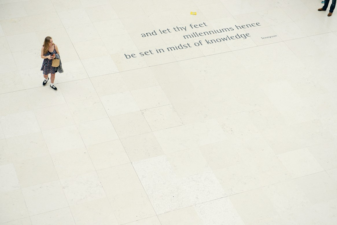 """A man and woman stand at either side of a quote written on the floor of the British Museum's great court reading """"and let thy feet millenniums hence be set in the midsts of knowledge"""""""