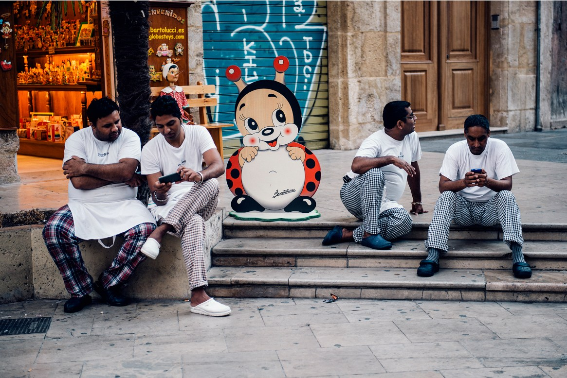 Four restaurant workers on a break outside a toy shop in Valencia, Spain.
