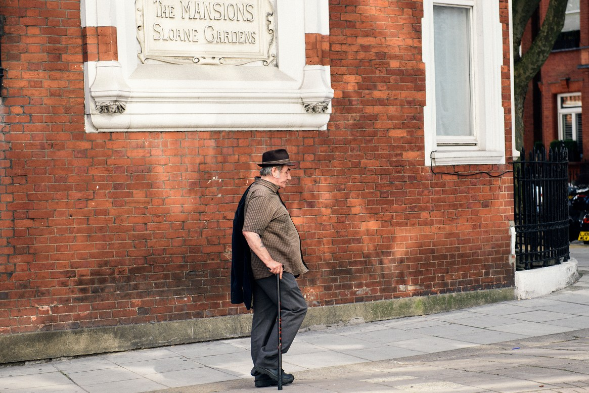 An old man wearing a hat walks past the brown brick wall of a classic West London mansion block