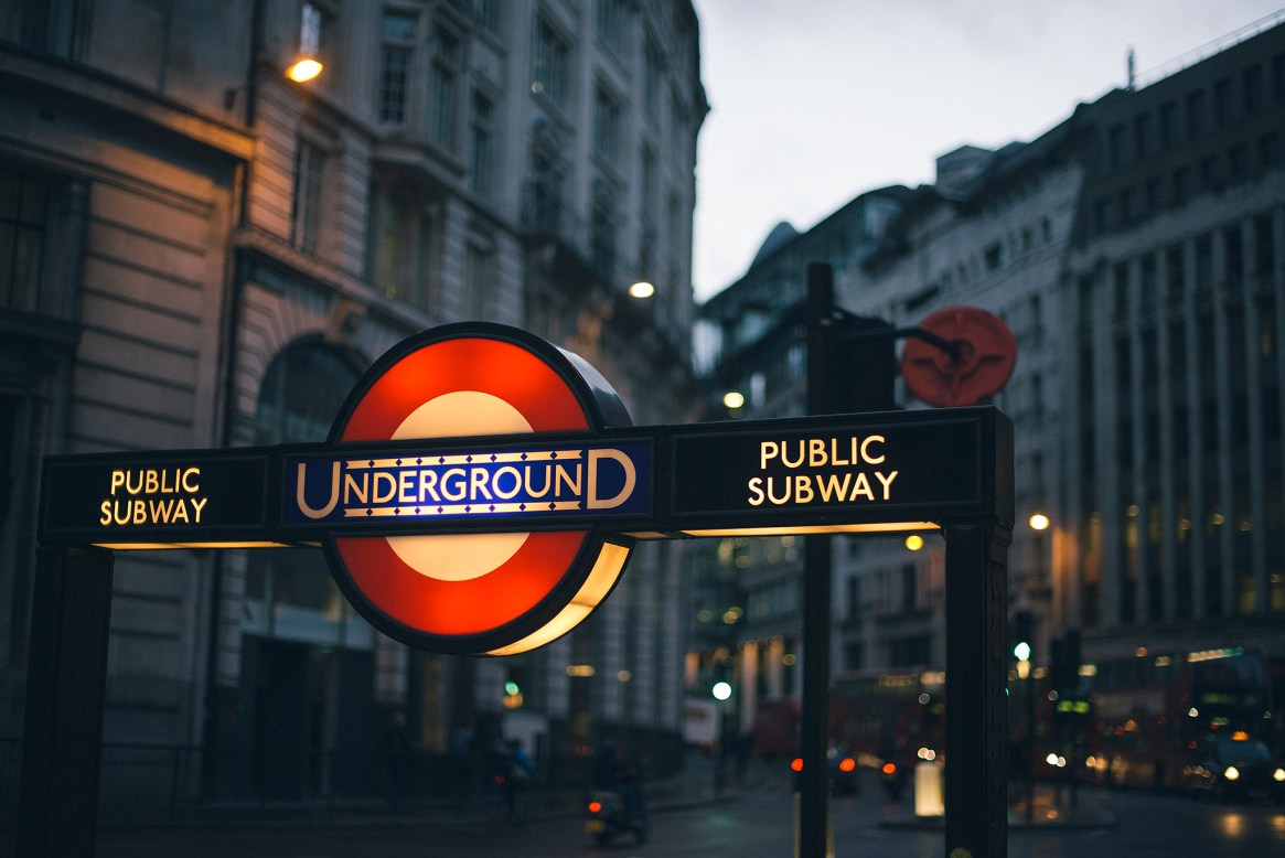 Low-light shot of London Underground / public subway sight set against city buildings at Monument in the City of London