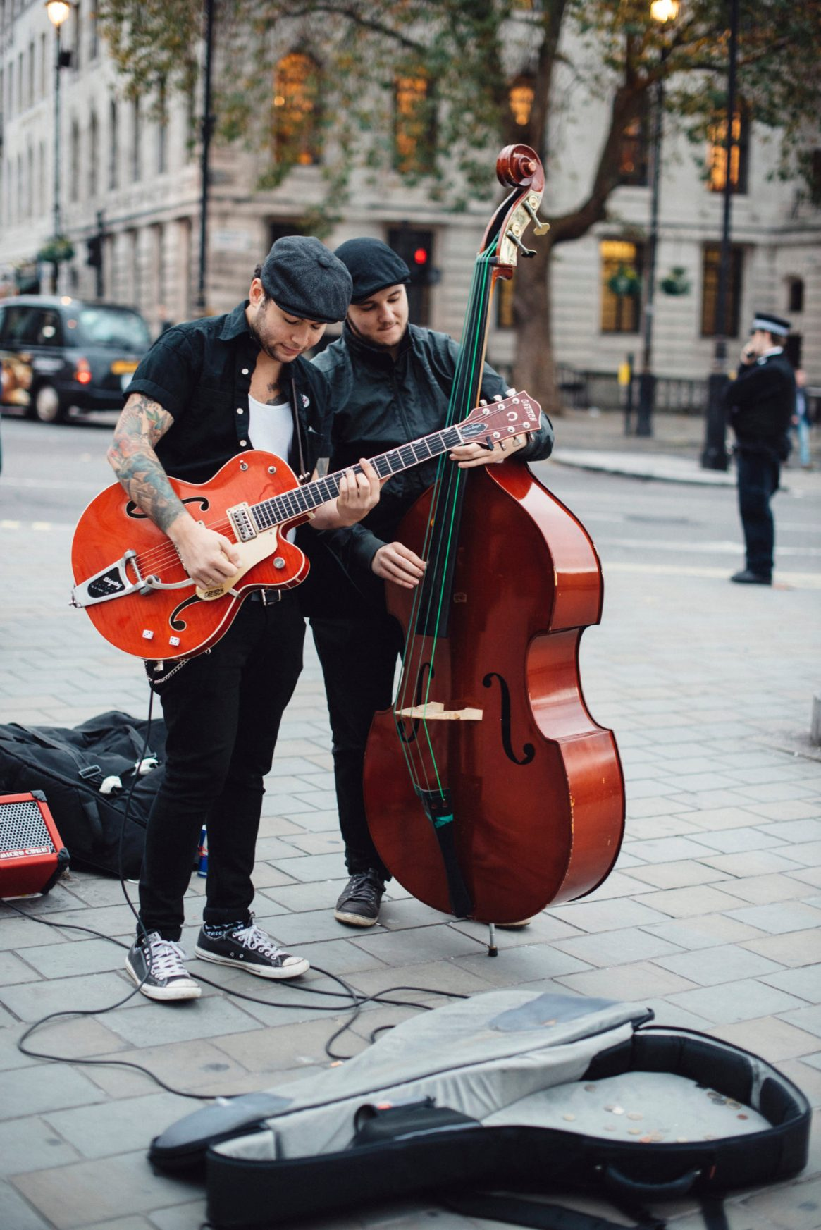 Two stylish musicians busking with guitar and double bass on Trafalgar Square in London