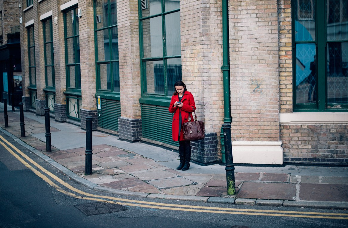 A woman in a bright red coat stands checking her phone in front of a green and brown brick wall in Shoreditch, London