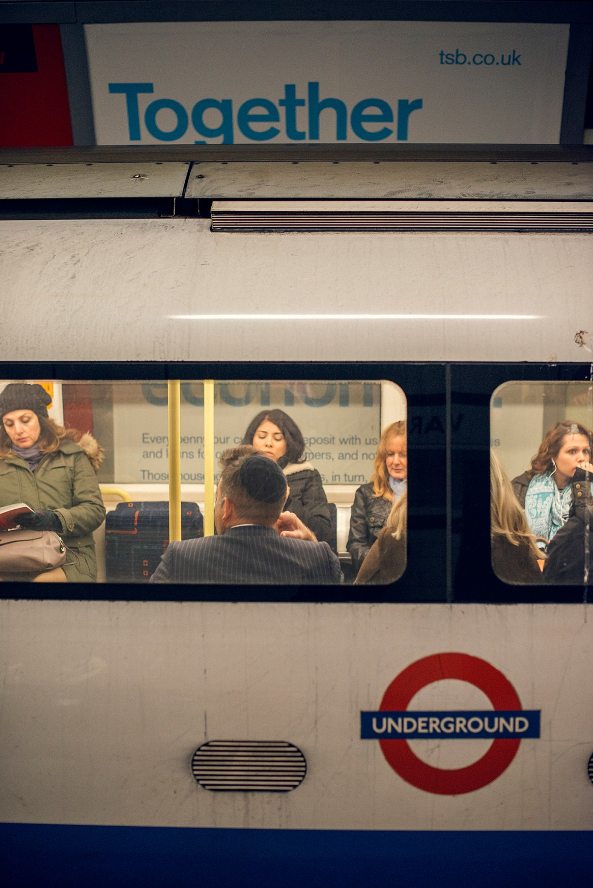 "Tightly framed portrait-orientation shot of a tube carriage showing the London Underground logo, parked in front of a giant poster reading ""Together"", with seated commuters visible through the carriage windows."