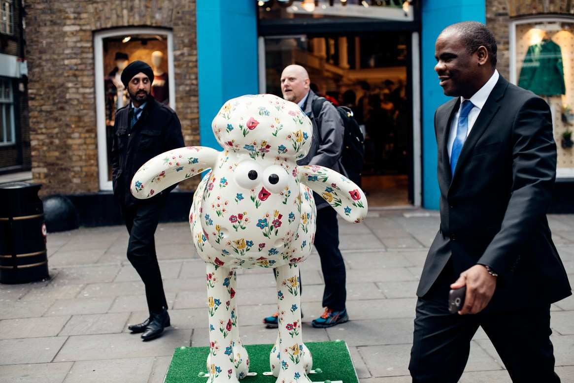 Three men dressed in black business suits walk past a comical floral-painted ceramic sheep
