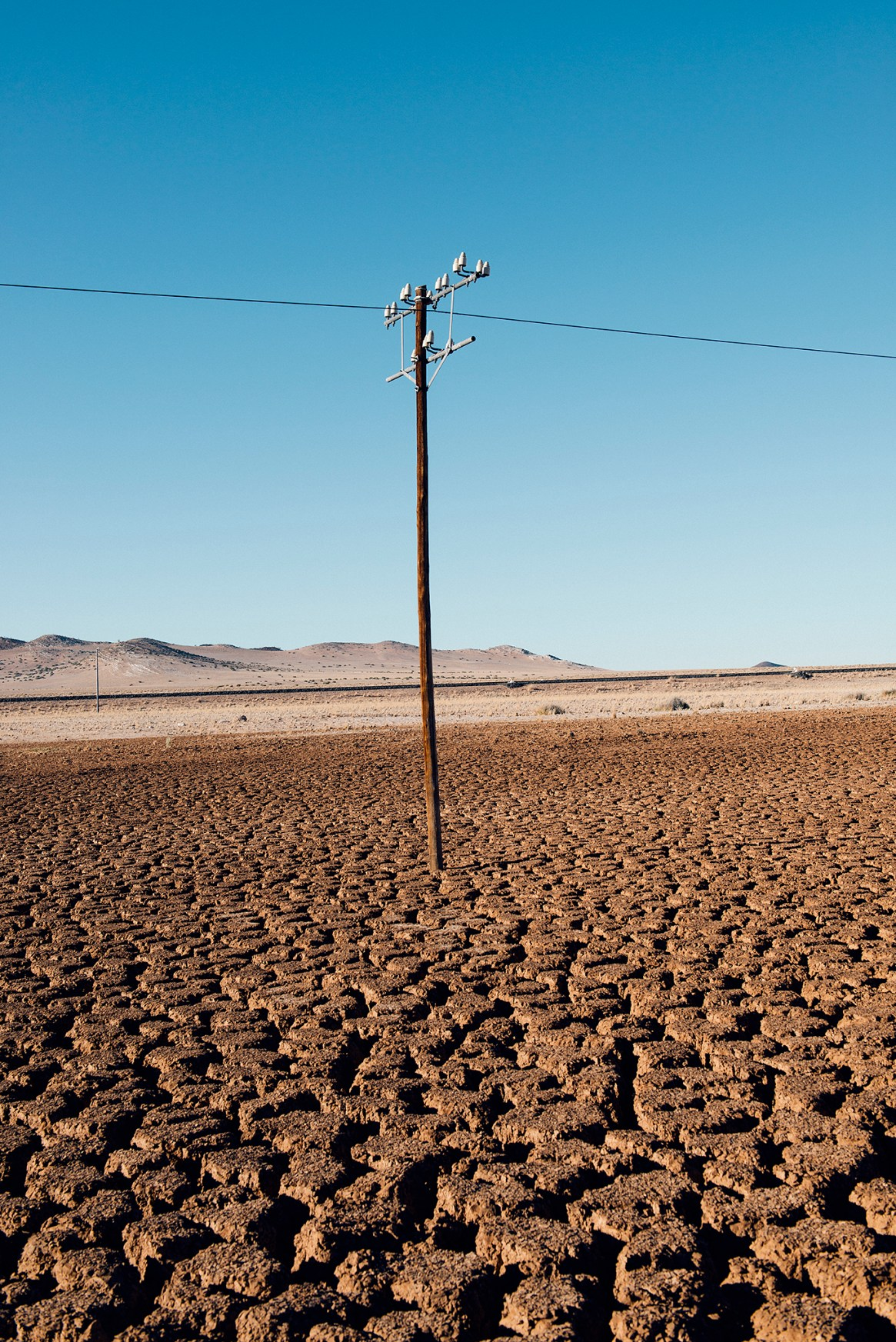 A solitary telephone pole planted in the crevassed semi-desert soil on the road between Aus and Luderitz in Namibia