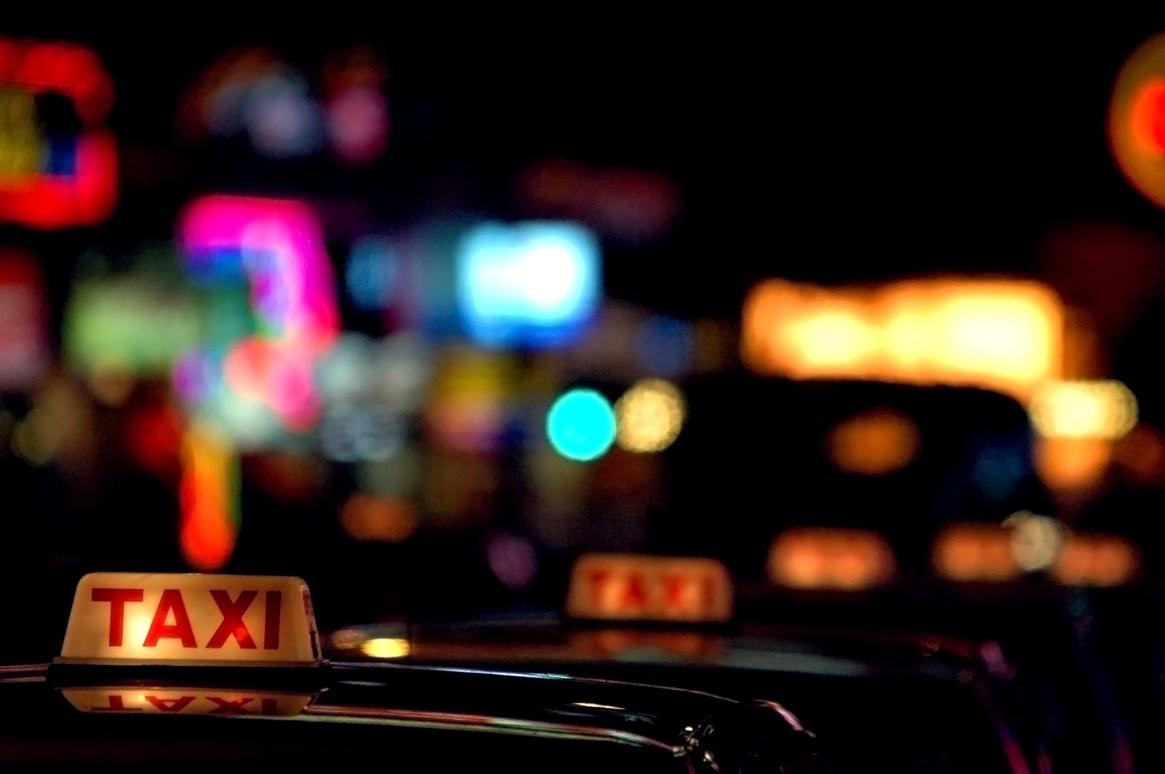 Hong Kong taxi rank with row of taxis at night