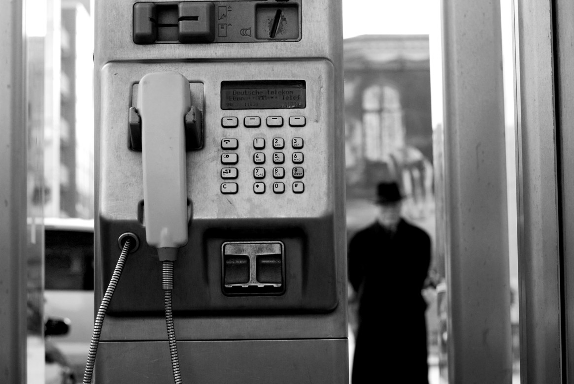 Black-and-white shot of an old man in a black coat next to a Deutsche Telekom payphone
