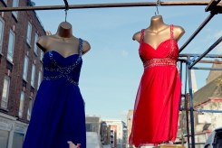Mannequins with red and blue dress hanging from a rail at street market