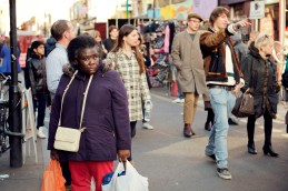 Black female shoppe walks down Brick Lane with her shopping
