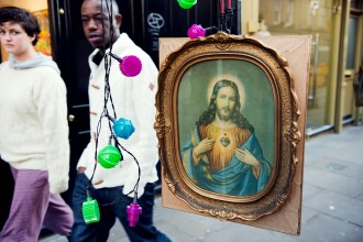 Painting of christ for sale at a street stall, with a couple walking past