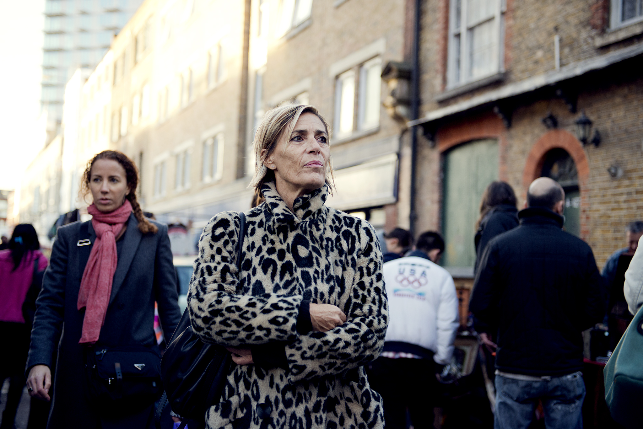 Woman in leopard print coat stares pensively into the distance