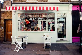 Green shopfront with tables and red awning
